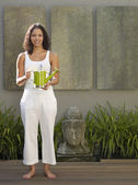 Mixed Race woman holding watering can — Stock Photo