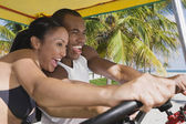 Multi-ethnic couple driving pedal cart — Stock Photo