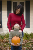Hispanic mother and daughter holding pumpkin — Stock Photo