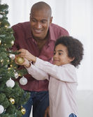 African father and son decorating Christmas tree — Stock Photo