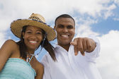 Multi-ethnic couple pointing and laughing — Stock Photo