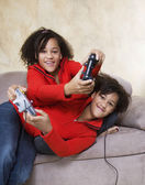 African twin sisters playing video games — Stock Photo