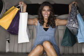 Middle Eastern woman holding shopping bags in limousine — Stock Photo