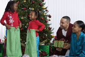 African sisters holding matching Christmas gifts — Stock Photo