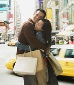 Asian couple hugging with shopping bags — Stock Photo