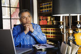 Hispanic man thinking at desk — Zdjęcie stockowe