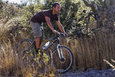 Hispanic man riding mountain bike — Stock Photo