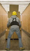 African warehouse worker carrying boxes — Stock Photo