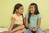 Pacific Islander sisters listening to mp3 player — Stock Photo
