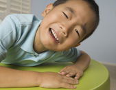 Asian boy crying on table — Stock Photo