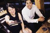 Asian couple paying restaurant bill — Stock Photo