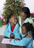 African mother and daughters writing letter to Santa Claus — Stock Photo
