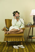 Asian woman in curlers talking on telephone — Stock Photo
