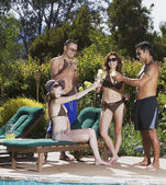 Multi-ethnic friends toasting next to swimming pool — Stock Photo