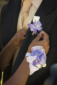 African teenaged girl fastening boyfriend's boutonniere — Stock Photo