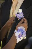 African teenaged girl fastening boyfriend's boutonniere — Stock Photo