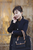 Asian woman talking on cell phone — Stock Photo
