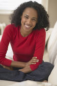 Mixed Race woman sitting on sofa — Stock Photo