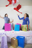 African twin sisters throwing clothing in air — Stock Photo