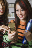 Multi-ethnic female hair stylists looking at hair product — Stock Photo