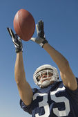 Hispanic male football player catching ball — Stockfoto