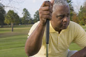African man holding golf club — Stock Photo