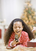 Mixed Race girl holding cell phone on Christmas — Stock Photo