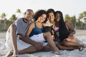 Multi-ethnic couples sitting on beach — Stock Photo