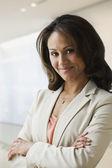 Hispanic businesswoman with arms crossed — Stock Photo