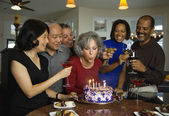 Woman celebrating birthday with multi-ethnic friends — Stock Photo