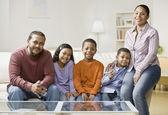 Mixed Race family sitting on sofa — Stock Photo