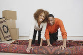 African couple rolling rug — Stock Photo