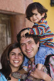 Hispanic family with son on father's shoulders — Stock Photo