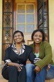 African mother and adult daughter sitting on porch steps — Stock Photo