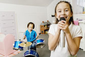 Asian sisters playing drums and singing — Stock Photo