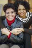 Mixed Race mother and adult daughter hugging — Stock Photo