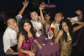 Multi-ethnic couples cheering at party — Stock Photo