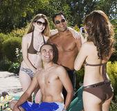Hispanic woman taking photograph of friends — Stock Photo