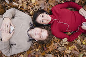 Multi-ethnic couple listening to mp3 players in autumn leaves — Stock Photo