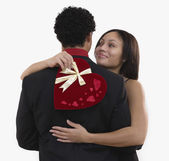 African woman holding valentine's gift and hugging boyfriend — Stock Photo