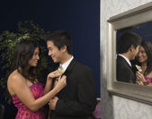 Asian woman fastening boyfriend's boutonniere — Stock Photo