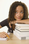 African woman leaning on stack of books — Stock Photo