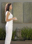 Mixed Race woman standing next to Buddha statue — Stock Photo