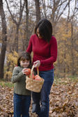 Hispanic mother and daughter holding basket of apples — Stock Photo