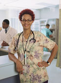 African female nurse leaning on counter — Stock Photo
