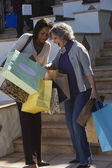 Multi-ethnic women looking in shopping bags — Stock Photo