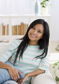 Pacific Islander woman sitting on sofa — Stock Photo