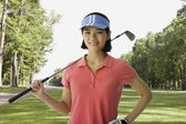 Asian woman holding golf club — Stock Photo