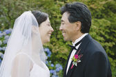 Asian newlyweds smiling at each other — Stock Photo