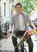 Azjatycki człowiek jazda rowerem z kwiaty w koszyku — Zdjęcie stockowe